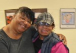 Author Sherri Winston gets a hug from former her former English teacher during a November 2012 visit to the Muskegon Heights Library in Muskegon Heights, Mich.